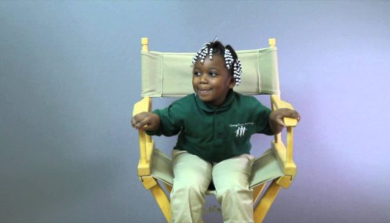 young female student sitting in a directors chair smiling