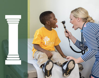 nurse using a scope to examine a young boys mouth