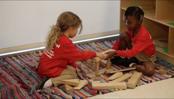 two children sitting on the classroom floor playing with building blocks