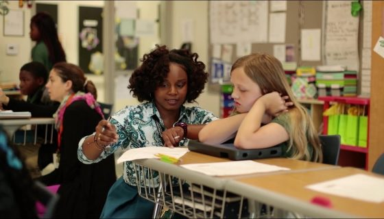 Teacher kneeling at a desk helping a young female student with her work