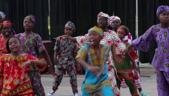 group of children dancing in traditional African clothing