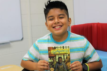 boy sitting down holding up a book and smiling