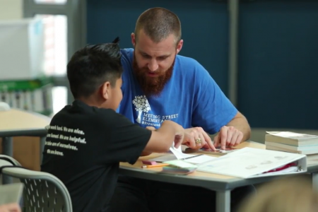 man sitting at a table helping a boy with homework
