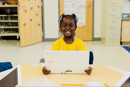 happy young girl in a classroom with a laptop