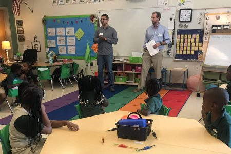 two men teaching a group of students in a classroom