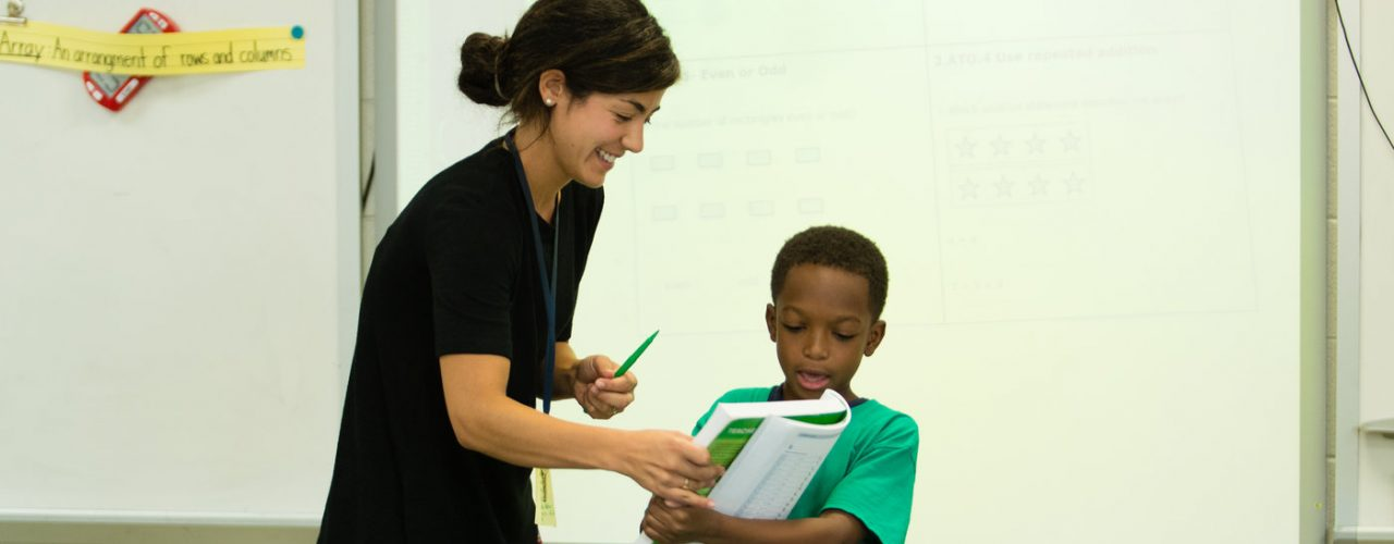 A young boy reading from a large textbook with a female teacher