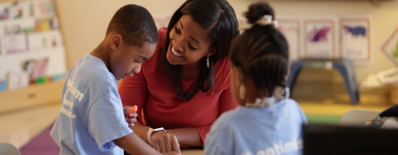 smiling female teacher playing with two students in a classroom