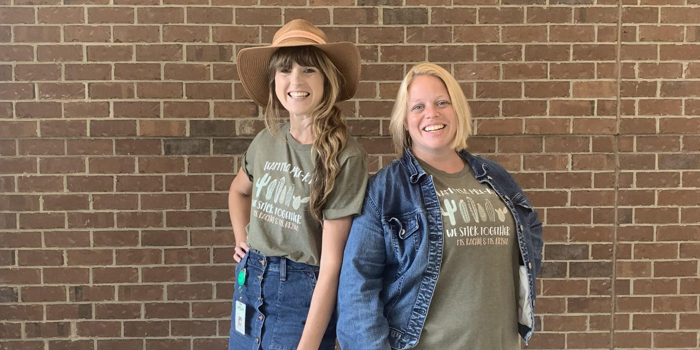 two female teachers in a fun pose with big smiles on their faces
