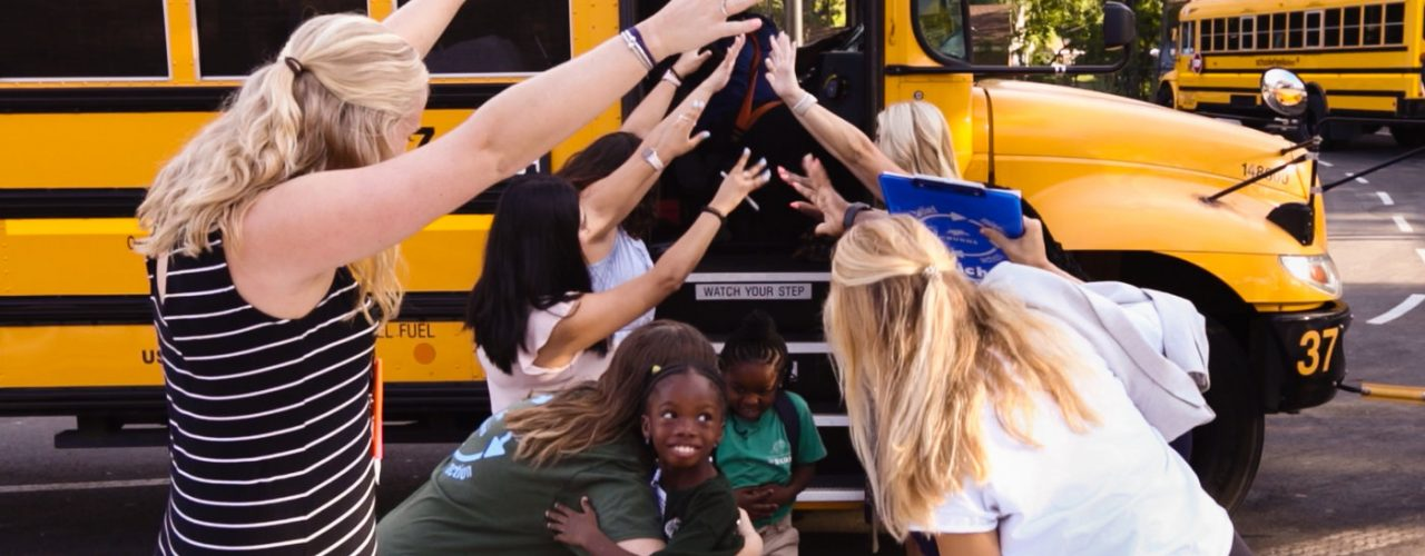 children getting off the bus are greeted by enthusiastic teachers