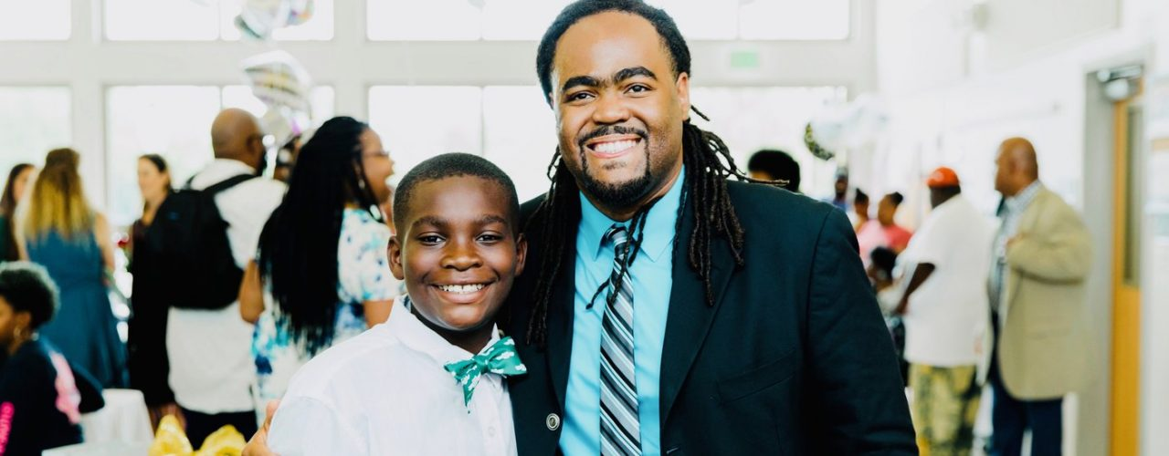 a young boy in a bow tie posing with a man in a suit and tie