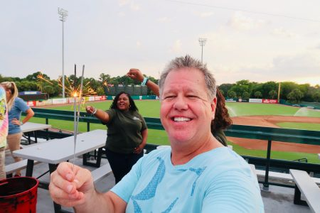 middle aged man smiling holding two sparklers at the baseball park